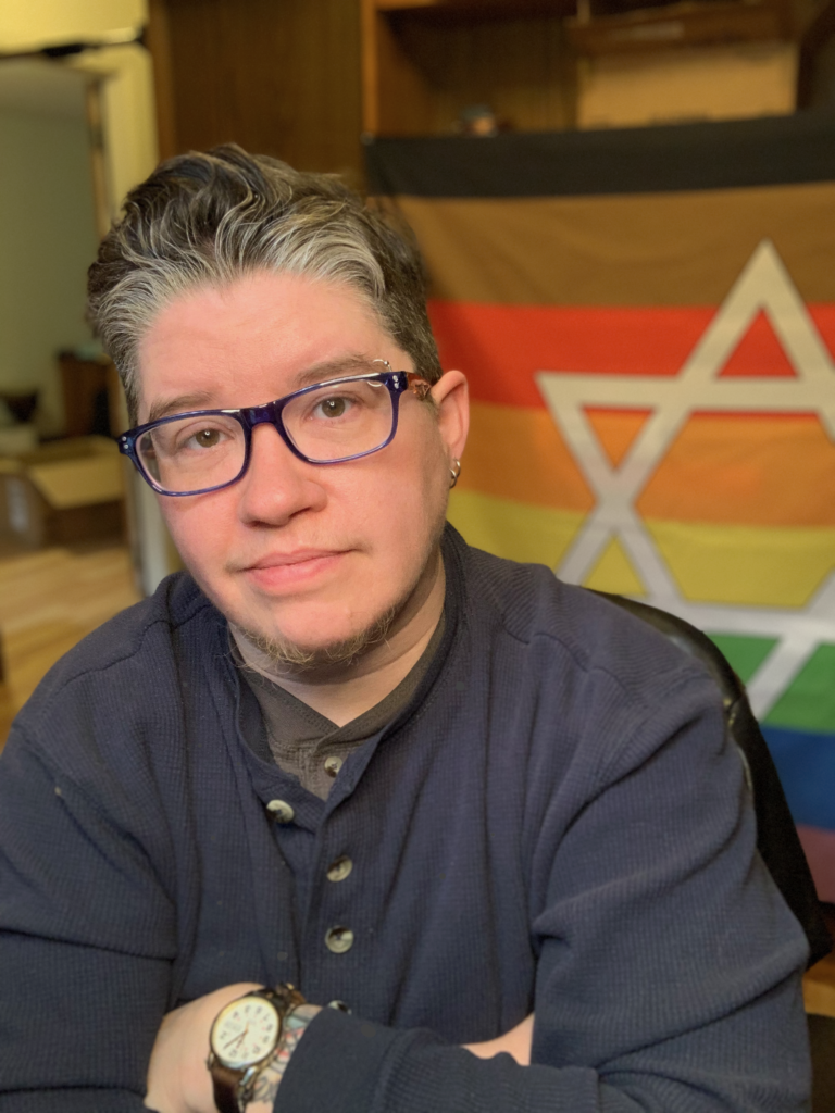 Photo of a white transgender man with short brown and gray hair, wearing glasses, sitting with arms crossed in front of a rainbow Pride flag with a Star of David on it